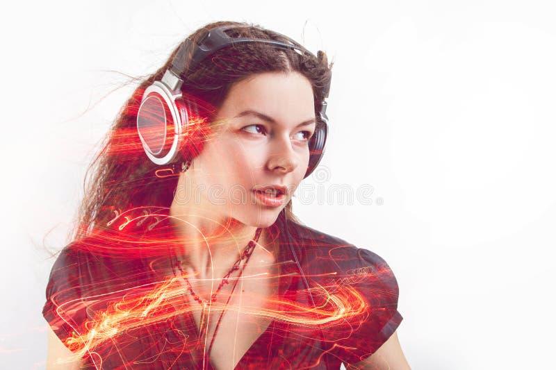 Dziewczyny fan śpiewa słuchanie i tanczy muzyka Młoda brunetki kobieta w dużych hełmofonach cieszy się muzykę obraz stock