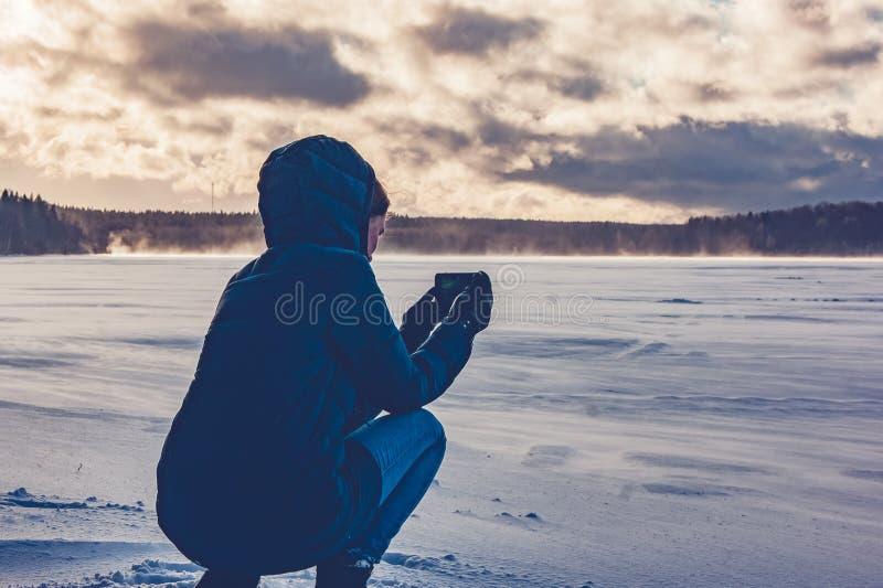 Dziewczyny fotografie na telefonie zamarznięty jezioro obraz stock