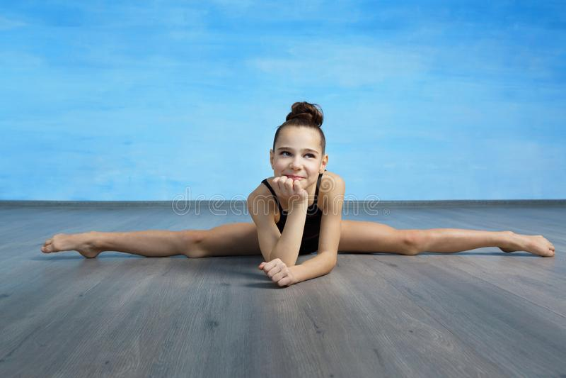Dziewczyny gimnastyczka w czarnym gimnastycznym swimsuit siedzi na krzy?a roz?amach na niebieskiego nieba tle zdjęcia stock