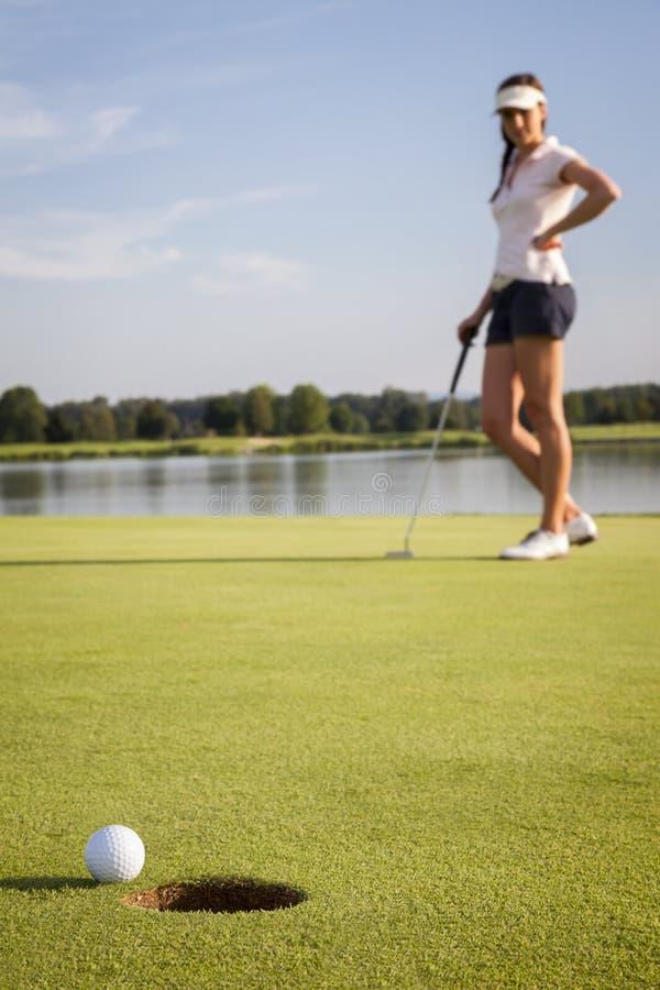 Dziewczyny golfowego gracza kładzenie na zieleni. zdjęcie stock