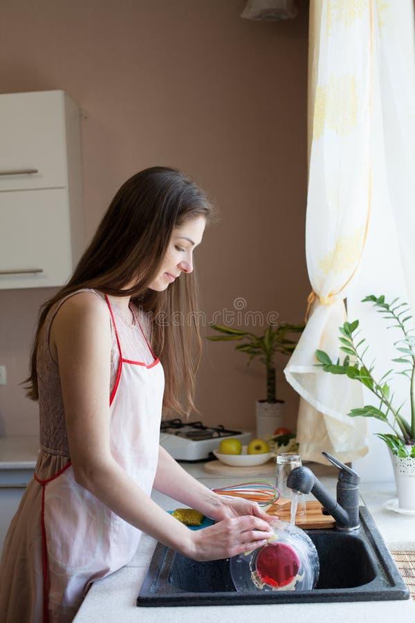 Dziewczyny gospodyni domowej obmycia brudzą naczynia w kuchni zdjęcie royalty free
