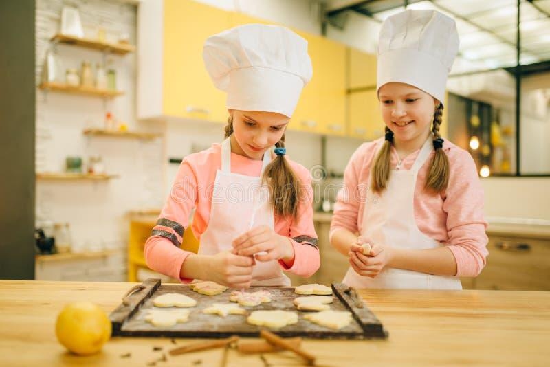 Dziewczyny gotują narządzanie wysyłać ciastka w piekarniku fotografia royalty free