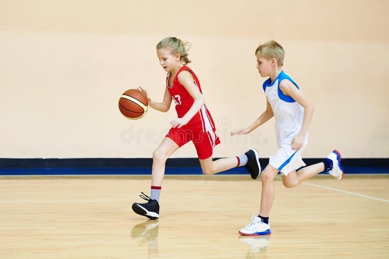 Dziewczyny i chłopiec atleta w mundurze bawić się koszykówkę fotografia royalty free