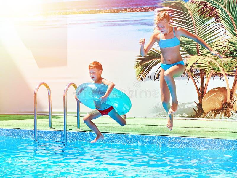 Dziewczyny i chłopiec doskakiwanie w kurortu basen fotografia royalty free
