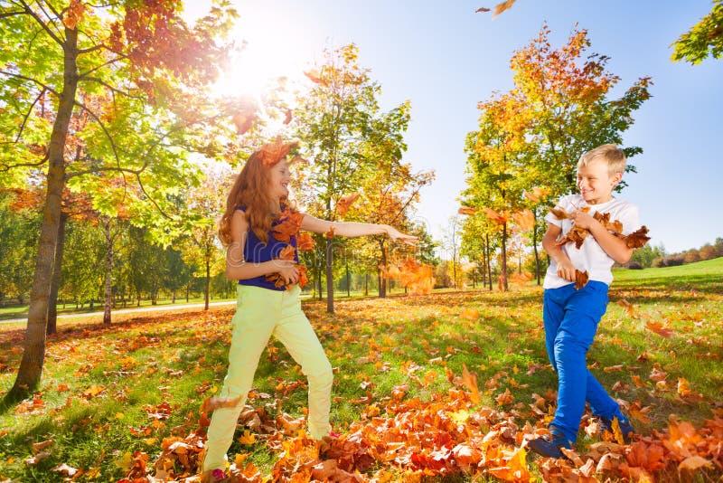 Dziewczyny i chłopiec sztuki miotanie opuszcza w lesie zdjęcie royalty free