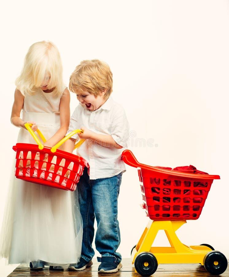 Dziewczyny i ch?opiec dzieci robi? zakupy Dzieciaka sklep Para dzieciak?w chwyta zakupy kosza plastikowa zabawka Zakup z rabatem  obrazy royalty free