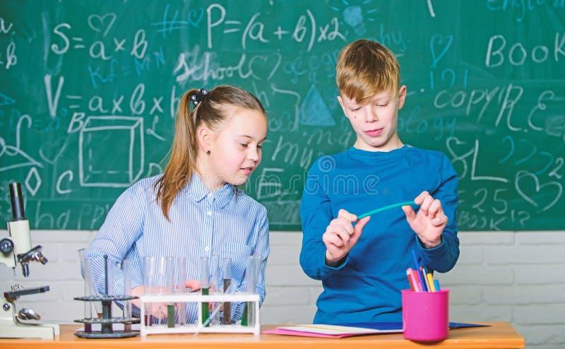 Dziewczyny i ch?opiec m?drze ucznie prowadz? szkolnego eksperyment Edukacja szkolna Chemiczna analiza ?artuje ruchliwie nauki che fotografia stock