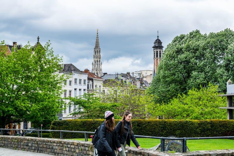 Dziewczyny idące po drzewie z pejzażem brukselskim z krajobrazem wieży ratowniczej na chmurnym niebie z Monts des zdjęcia stock