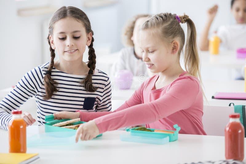 Dziewczyny je zdrowego śniadanie w szkole zdjęcia royalty free
