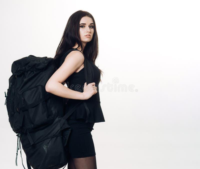 Dziewczyny klasycznego czerni smokingowy i turystyczny plecaka wyposażenie Elegancja i pakowność Kobieta niesie bagaż na ona z po obrazy stock