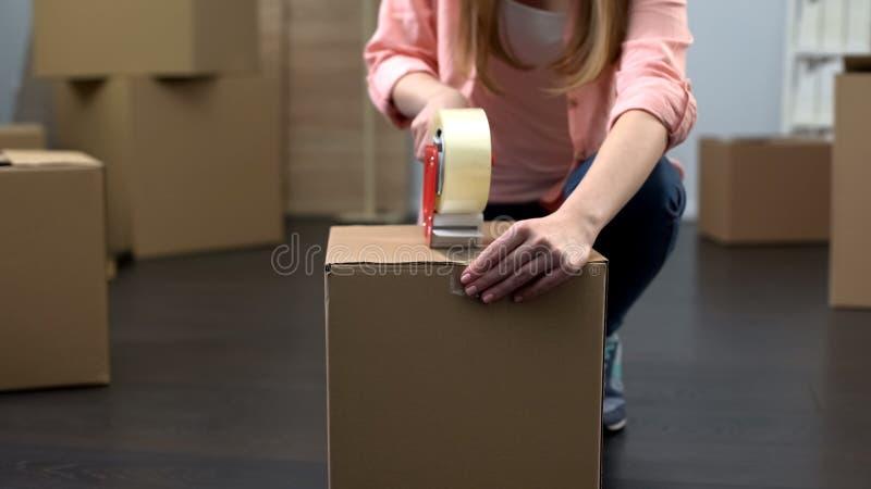 Dziewczyny kocowania pudełka z materiałem, rusza się od mieszkania, końcówka czynszu kontrakt zdjęcie stock