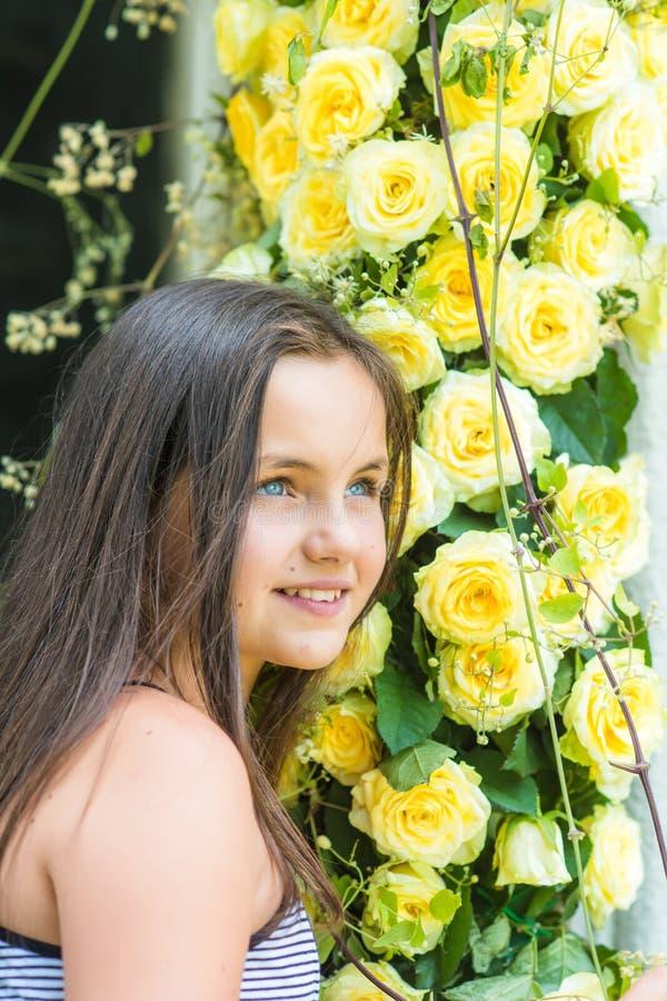 Dziewczyny kwiaciarni stojak przy żółtymi różami w kwiatu sklepie obraz stock