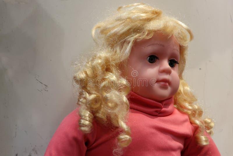 Dziewczyny lala z złotym włosy, jest ubranym czerwoną koszula obraz stock