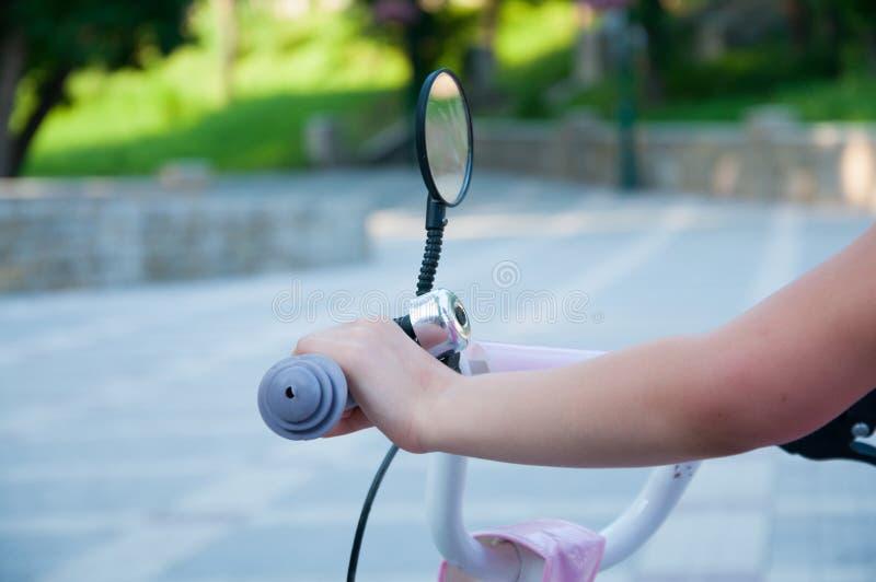 dziewczyny lewa ręka na rowerowych handlebars W parku na alei podczas gdy chodzący obrazy stock