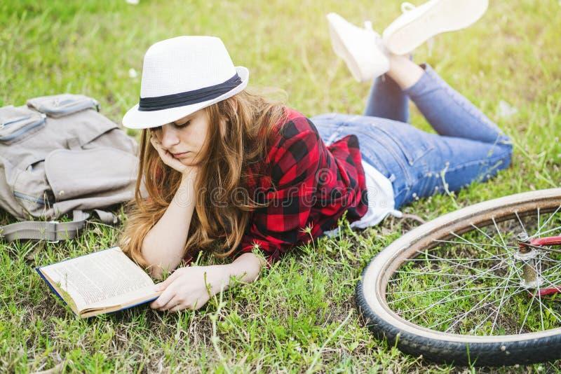 Dziewczyny lying on the beach i czytelnicza książka na trawie zdjęcia royalty free