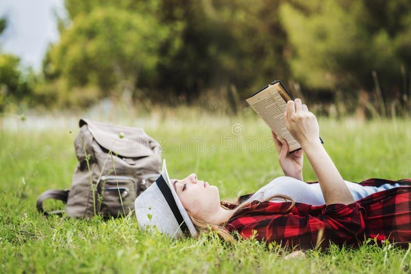 Dziewczyny lying on the beach i czytelnicza książka na trawie fotografia stock