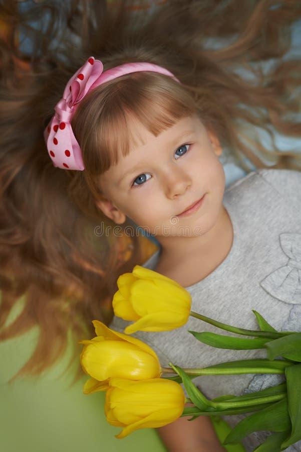 Dziewczyny lying on the beach na podłoga z tulipanami jako teraźniejszość dla matki obrazy royalty free
