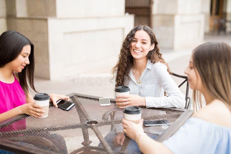 Dziewczyny ma kawę przy plenerową kawiarnią obraz royalty free