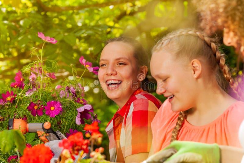 Dziewczyny ma zabawę podczas gdy zasadzać kwitnie outdoors zdjęcia royalty free