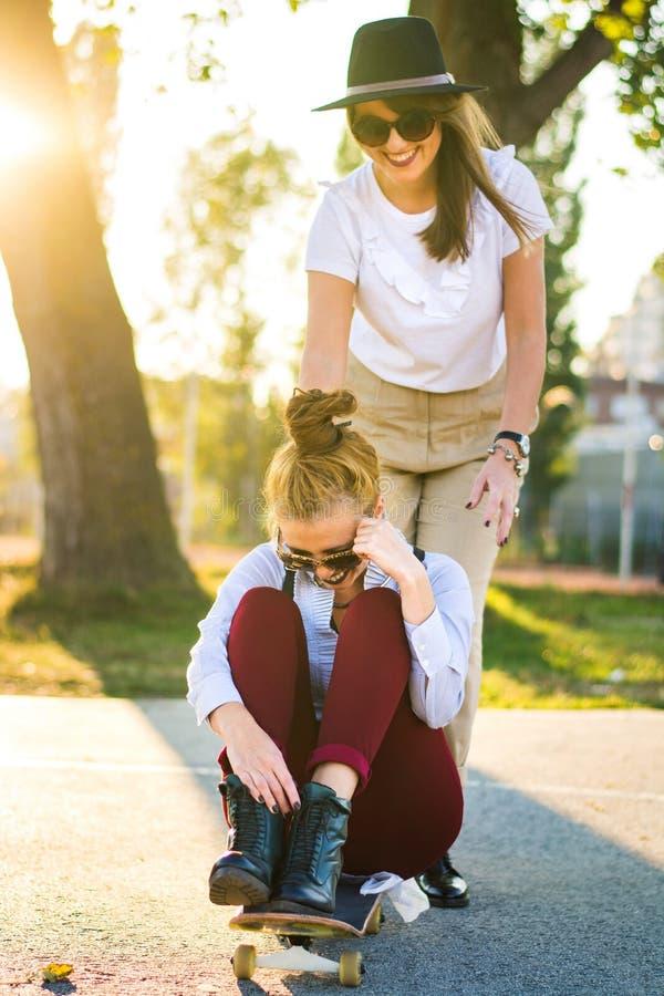 Dziewczyny ma zabawę z deskorolka w parku fotografia royalty free