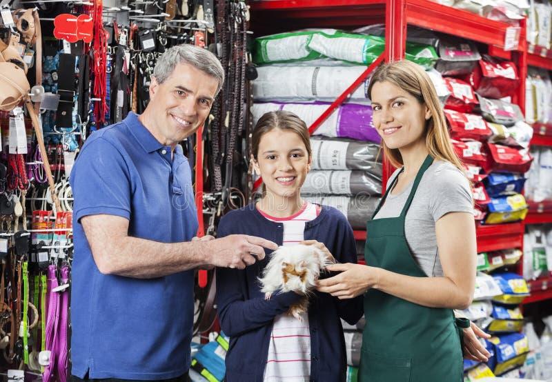 Dziewczyny mienia królik doświadczalny Z ojcem I sprzedawczynią W sklepie fotografia royalty free