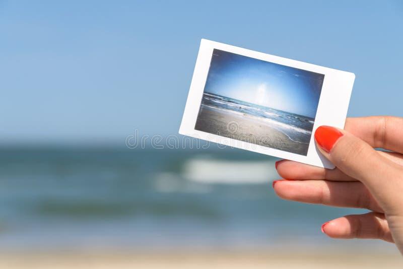 Dziewczyny mienia Natychmiastowa fotografia morze plaża fotografia royalty free