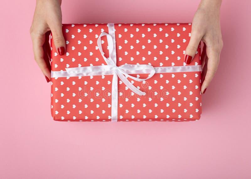 Dziewczyny mienia prezent w rękach, pudełkowaty zawijający w dekoracyjnym papierze na pastelu barwił różowego tło, odgórny widok, obrazy stock