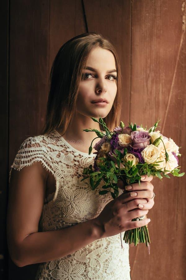 Dziewczyny mienie kwitnie w rękach, młoda piękna panna młoda w białym dr fotografia stock