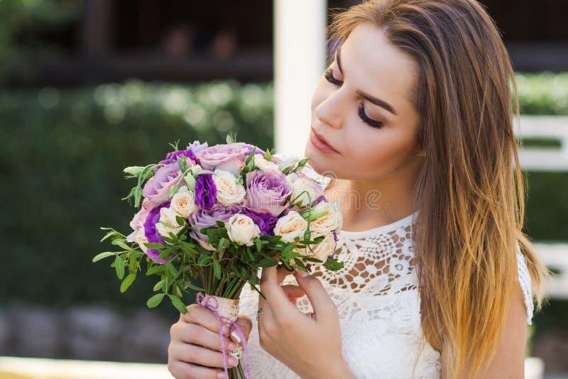 Dziewczyny mienie kwitnie w rękach, młoda piękna panna młoda w białym dr obrazy royalty free