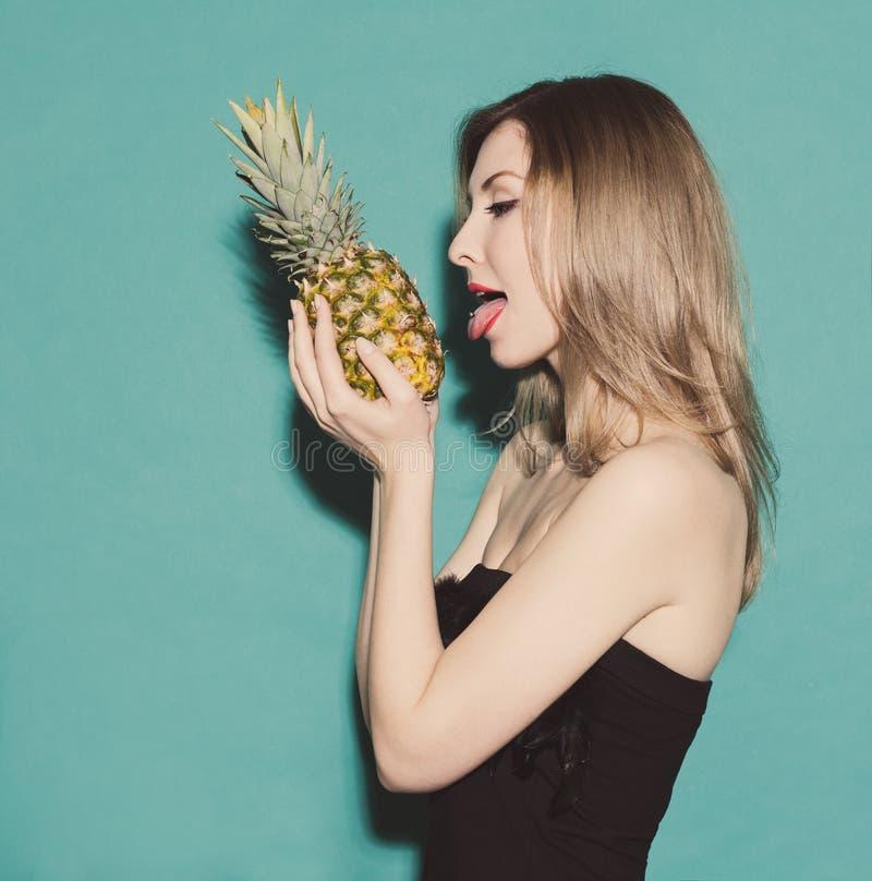 Dziewczyny mienie wręcza ananasa i dosięga dla jego jęzoru w czarnej sukni na zielonym tle w studiu Stonowany kolor Pojęcie fotografia royalty free