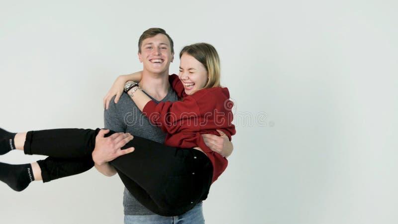 Dziewczyny miotanie herself w rękach jej chłopak na białym tle Młoda dziewczyna skacze na chłopak ręce fotografia royalty free