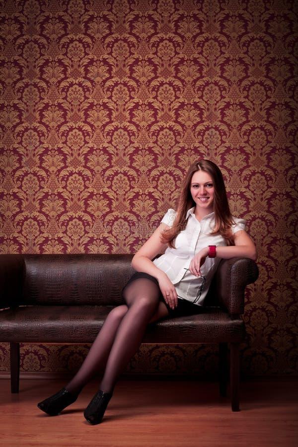 dziewczyny obsiadania uśmiechnięta kanapa fotografia royalty free