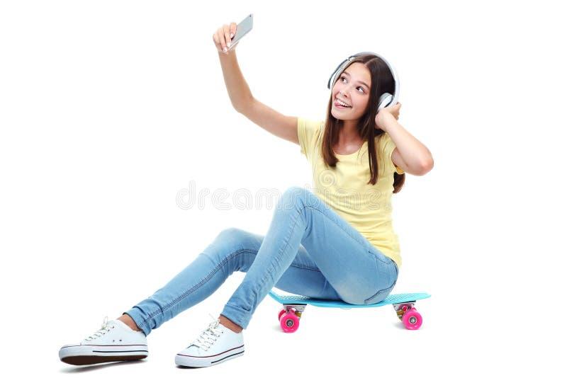 Dziewczyny obsiadanie na deskorolka z he?mofonami zdjęcia stock
