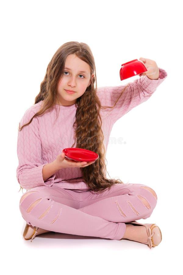 Dziewczyny obsiadanie na podłodze demonstruje przestawną filiżankę, mówić że ono jest pusty obraz royalty free