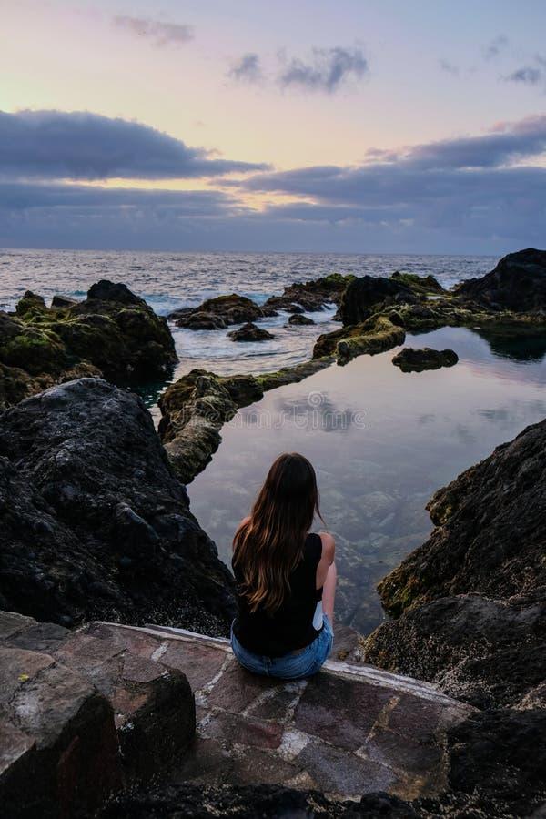Dziewczyny obsiadanie na powulkanicznych skałach patrzeje naturalnego basenu i morza zdjęcia stock