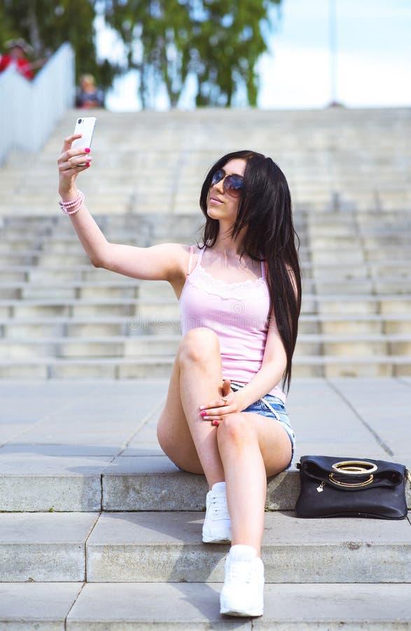 Dziewczyny obsiadanie na schodkach, w ulicie robi twój telefonowi pięknej jaźni zdjęcia stock