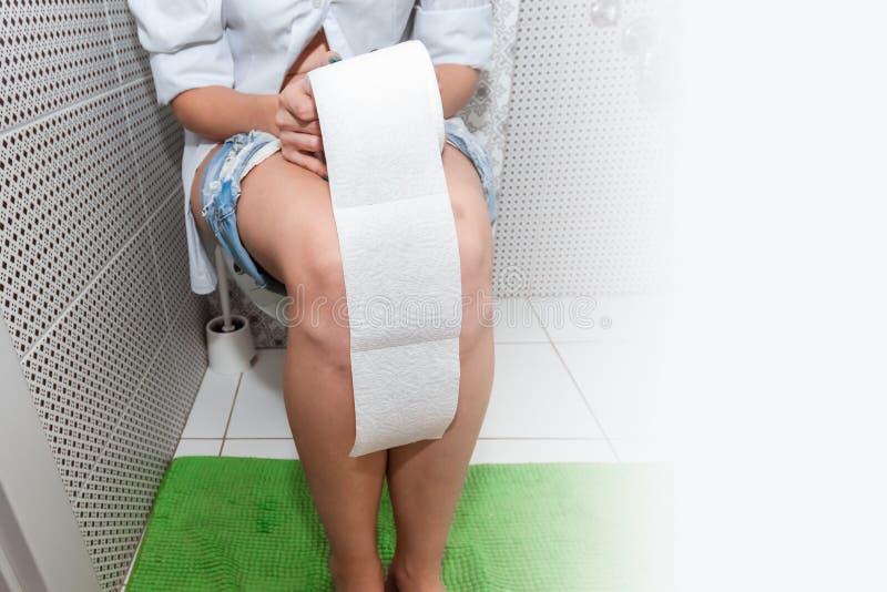 Dziewczyny obsiadanie na toalecie trzyma papier toaletowego Pojęcie problemy z krzesłem, jelita, osobista higiena, obraz stock