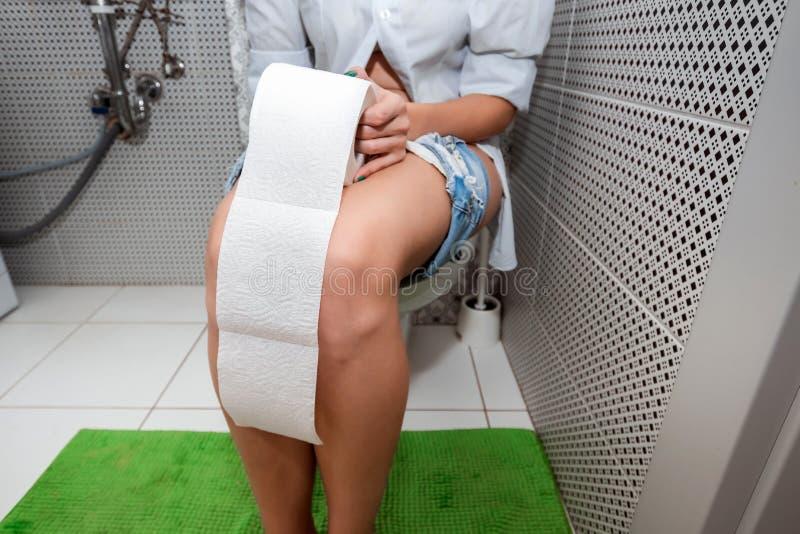 Dziewczyny obsiadanie na toalecie trzyma papier toaletowego Pojęcie problemy z krzesłem, jelita, osobista higiena, fotografia royalty free
