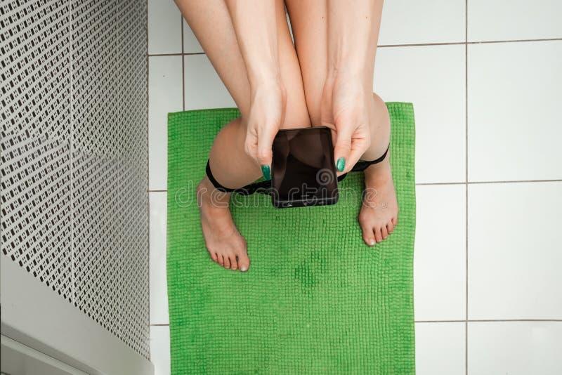 Dziewczyny obsiadanie na toaletowym mieniu smartphone w jej rękach, odgórny widok Pojęcie problemy z krzesłem, jelita, zdjęcia stock