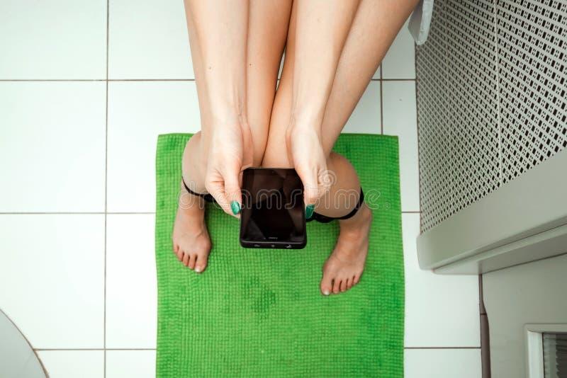 Dziewczyny obsiadanie na toaletowym mieniu smartphone w jej rękach, odgórny widok Pojęcie problemy z krzesłem, jelita, fotografia stock