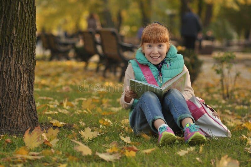 Dziewczyny obsiadanie na trawy książce z książką, śmieszny wyrażenie na jego twarzy zdjęcia royalty free