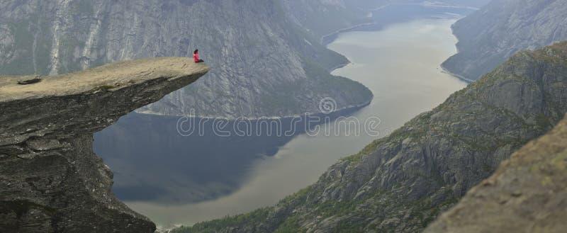 Dziewczyny obsiadanie na Trolltunga w Norwegia fotografia stock