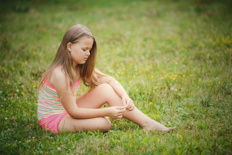 Dziewczyny obsiadanie na zielonej trawie plenerowej zdjęcia stock