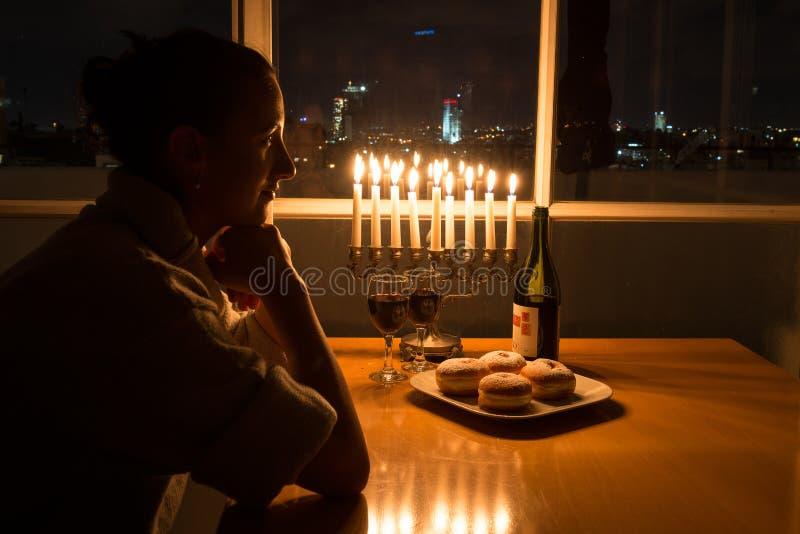 Dziewczyny obsiadanie okno z menorah świętuje Hanukkah