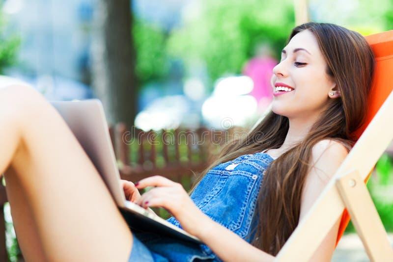 Dziewczyny obsiadanie w deckchair używać laptop fotografia royalty free