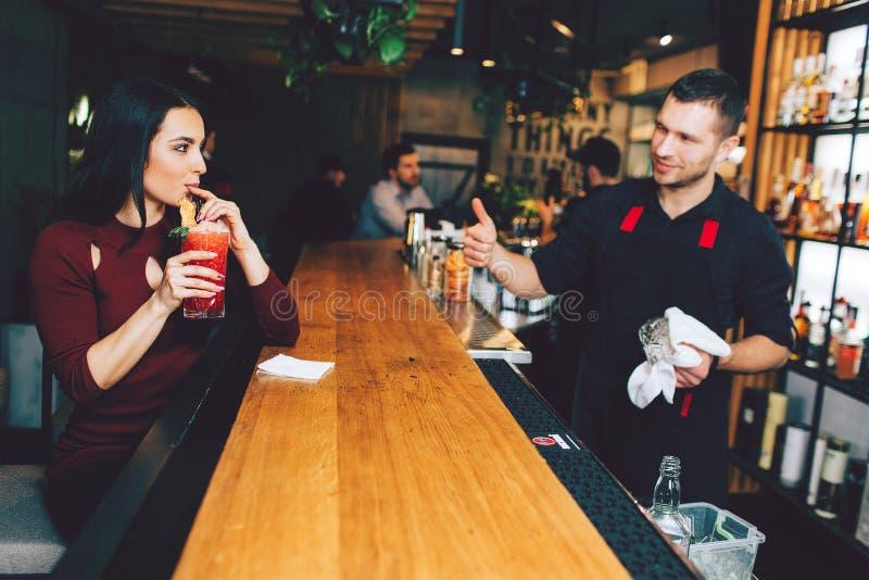 Dziewczyny obsiadanie w pić koktajlu i barze który rozkazywał Lubi mnie Barman jest szczęśliwy jego klient satysfakcjonuje obraz stock