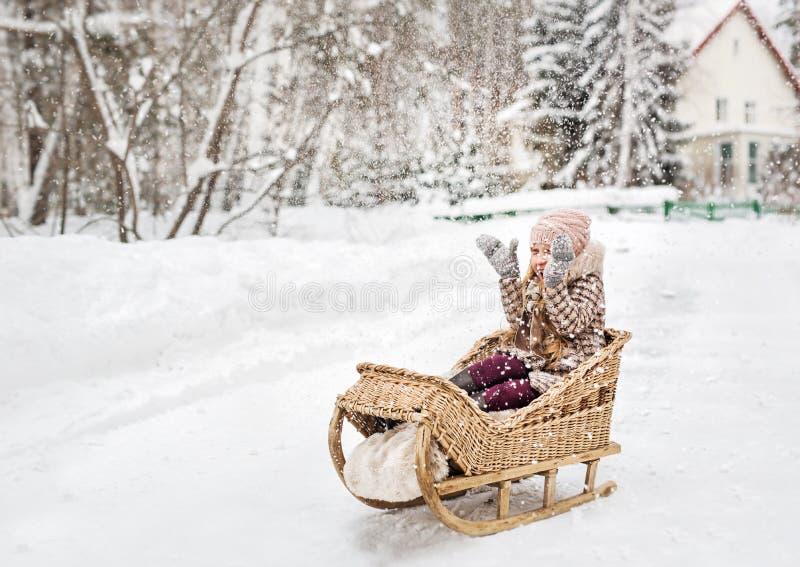Dziewczyny obsiadanie w rocznika drewnianym saniu i szczęśliwie zakrywać jego ręki od śniegu zdjęcie royalty free