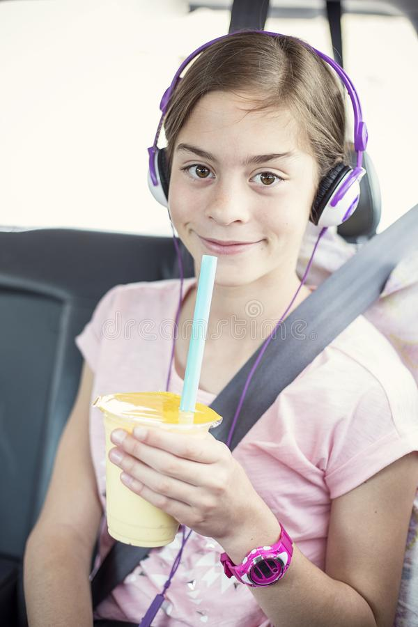 Dziewczyny obsiadanie w samochodowym siedzeniu słucha muzyka na długiej samochodowej przejażdżce obraz royalty free