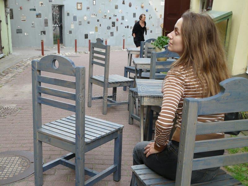Dziewczyny obsiadanie w ulicznej kawiarni w małej malowniczej wąskiej ulicie Stary Grodzki Vilnius Lithuania obraz royalty free