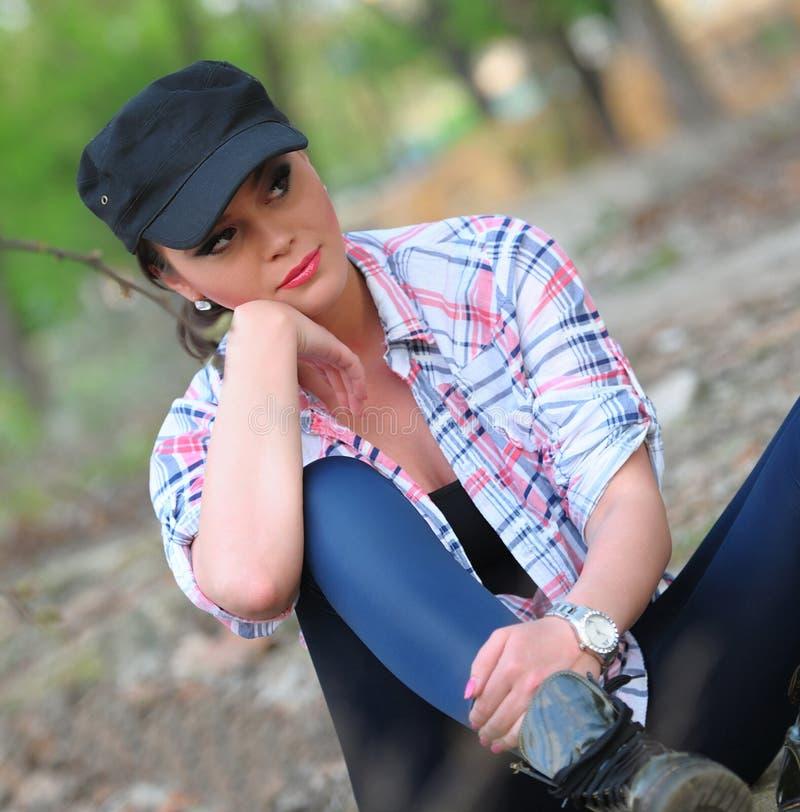 Dziewczyny obsiadanie z kolorową koszula, leggings i nakrętką na głowie, fotografia stock